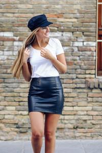 Young blonde woman wearing cap smiling near a brick wall