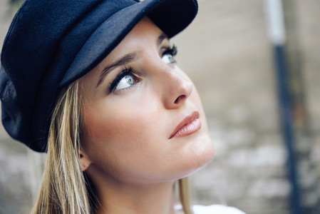 Young blonde woman wearing cap in urban background