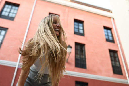 Happy young woman with moving hair in urban background