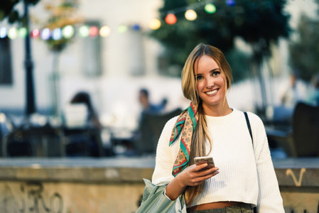 Woman with defocused urban city lights with smartphone