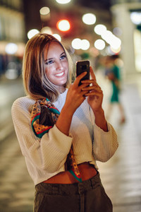 Woman taking photograph with smartphone at night in the street
