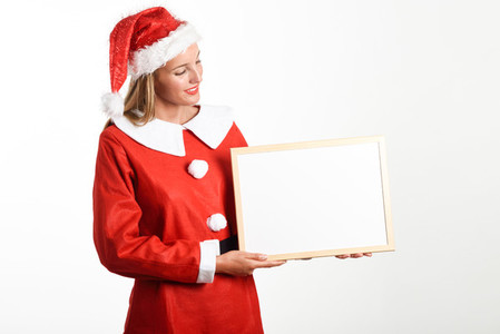 Smiling blonde woman in Santa Claus clothes with white board