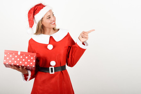 Blonde woman in Santa Claus clothes smiling with gift box