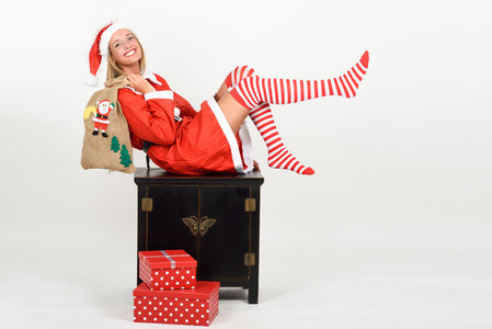 Funny blonde woman in Santa Claus clothes on white background