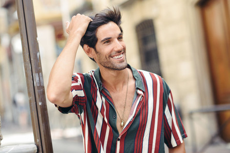 Smiling young man touching his hair wearing casual clothes outdoors