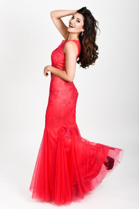 Young woman wearing long red dress on white background