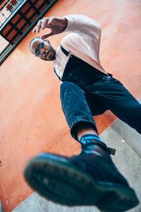 Young black man man kicking towards the ground