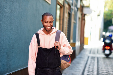 Young black man walking smiling down the street