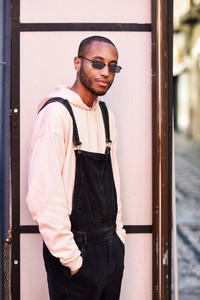 African guy with bib pants standing outdoors