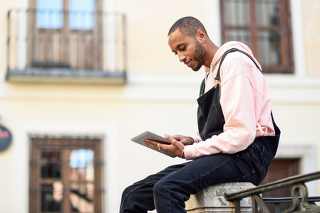 Young black man using digital tablet in urban background