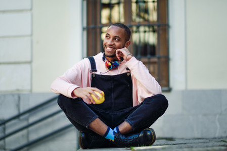 Young black man eating an apple sitting on urban steps