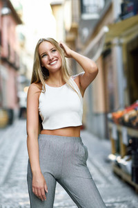 Beautiful young blonde woman smiling in urban background