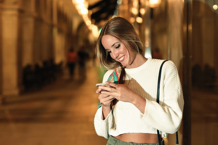 Woman with defocused urban city lights looking at her smartphone