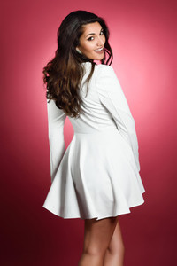 Young woman wearing short white dress smiling to camera