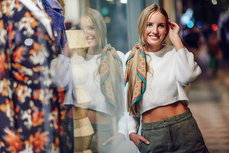 Blonde girl smiling with defocused urban city lights at night