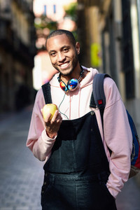 Young black man eating an apple walking down the street