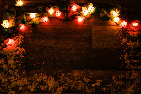 Christmas lights on dark wooden board