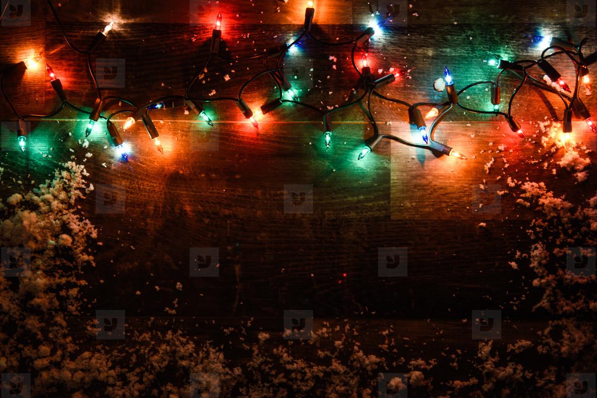 Christmas lights on dark wooden board