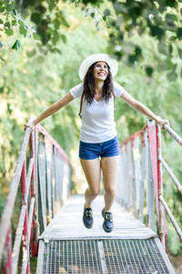 Woman with backpack standing on rural bridge