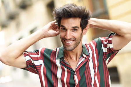 Smiling young man with dark hair and modern hairstyle wearing casual clothes outdoors
