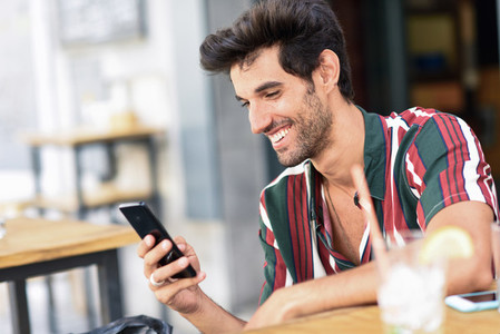 Young man using smartphone in an urban cafe