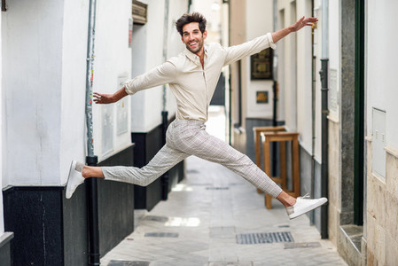 Young happy man jumping in the street