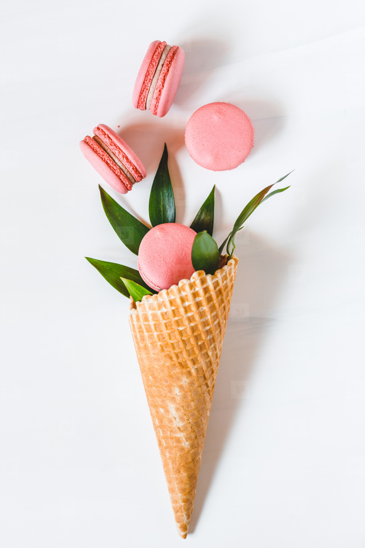 Spring abstract bouquet with a waffle cone  coral macaroons and green plant on a white background  Top view  flat lay