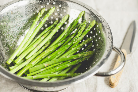 Washed asparagus in a metal colander on a kitchen table Preparation vegetarian healthy food