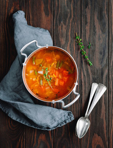 Spring vegetable soup with chicken stock in a pot on kitchen wooden table  Rustic style  close up view