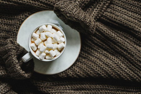 Flat lay of hot chocolate with marshmallow in a ceramic mug over dark green knit winter sweater  The concept of cosy days and Fall  top view