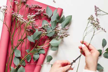 Girl creates a bouquet from spring flowers and eucalyptus branch on a white table The concept of florists work and flora top view flat lay