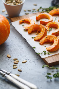 Baked pumpkin slices with thyme on a wooden board over grey table  Seasonal food vegetarian recipe  Copy space