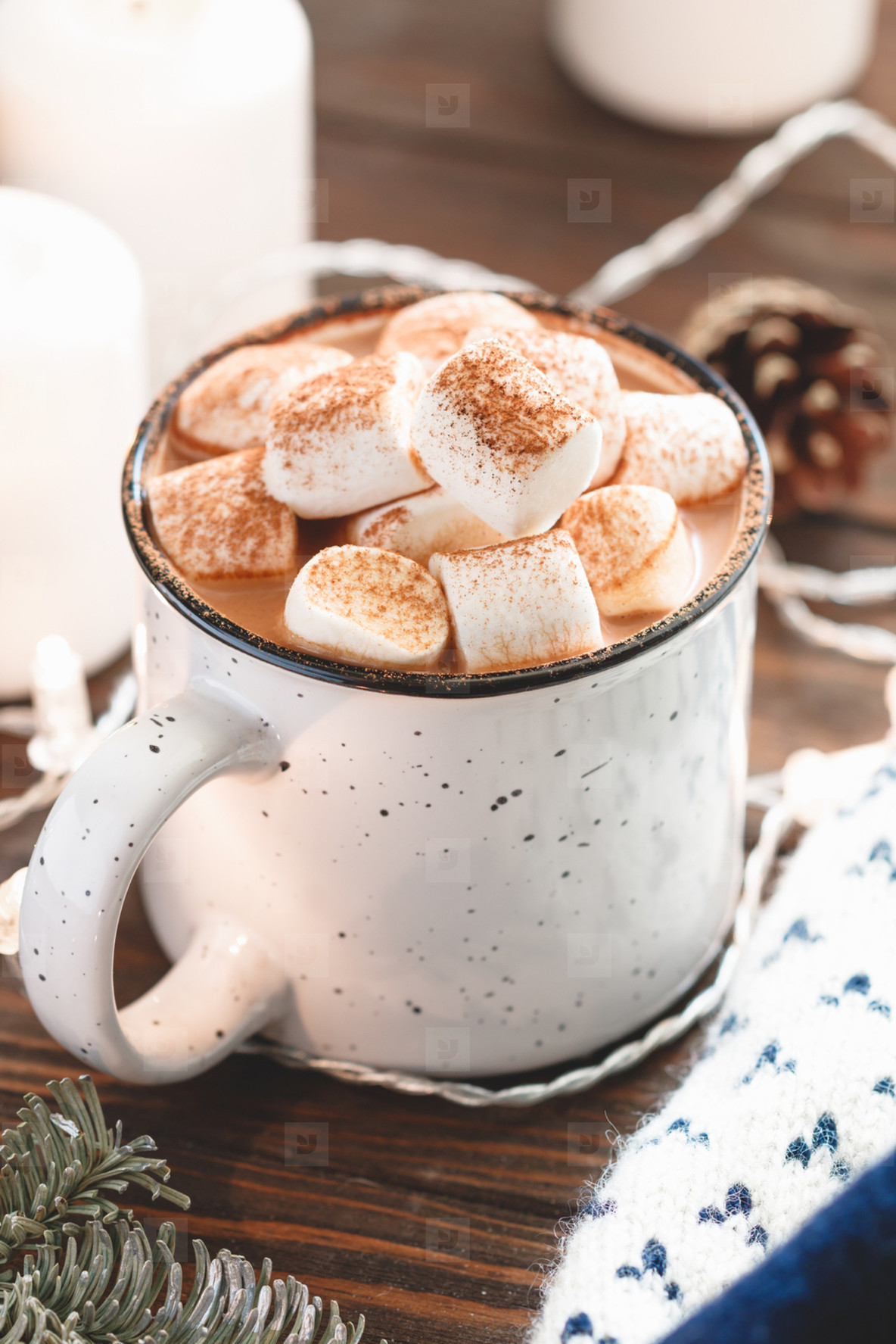 Hot chocolate with marshmallow in a white ceramic mug among winter things and decor on a wooden table  The concept of cosy holidays and New Year