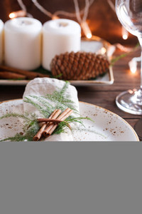 Linen napkin decorated cinnamon sticks and plants on a ceramic plate The concept of Christmas or Thanksgiving dinner and decorating table settings
