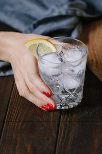 The womans hand holds the cocktail with club soda vodka lemon and ice on a wooden table Retro or vintage toned image