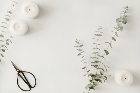 Creating of a bouquet with baby blue eucalyptus branch among white candles on a table The concept of a florist work or celebration  Top view flat lay
