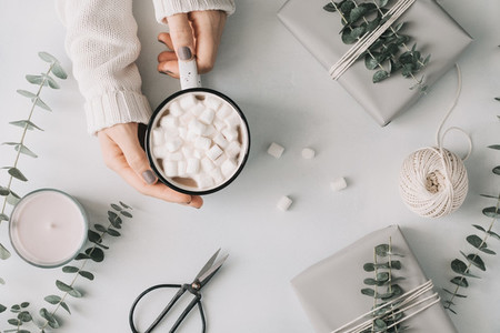 Girls hands hold a mug with hot chocolate and marshmallow among gift boxes and eucalyptus on a white table The concept of wintertime and wrapping gifts Flat lay top view minimal style