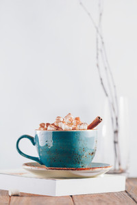 Hot chocolate with marshmallows and cinnamon stick in a blue ceramic cup on a table with a book The concept of winter or fall time Minimal scandinavian design