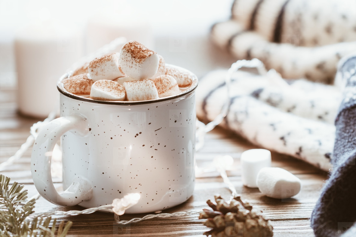 Hot cocoa with marshmallow in a white ceramic mug surrounded by winter things on a wooden table  The concept of cosy holidays and New Year