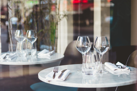 Table setting in a French restaurant for two  View through a window from a street