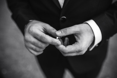 groom holding a wedding ring