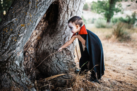 Kid serious costumed of dracula to halloween on the forest