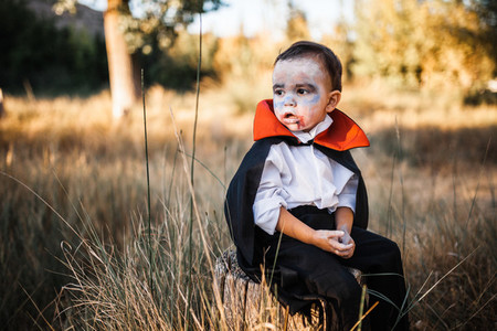 Kid painting himself of dracula to halloween on the forest
