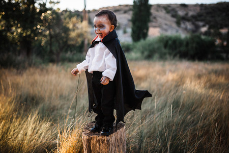 Kid smiling costumed of dracula to halloween on the forest