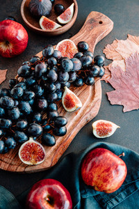 Autumn food still life with season fruits and vegetables like Bangalore blue grape red apples and figs on a table