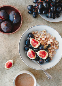 Top view of a breakfast bowl with granola blue grape and fig slices Healthy vegan eating flat lay