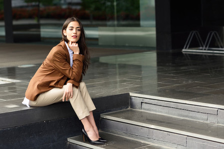 Young businesswoman sitting outside of office building in urban