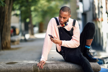 Young black man using smart phone outdoors