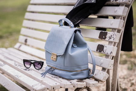 Bag sunglasses and leather jacket on a bench