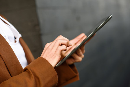 Businesswoman with tablet computer standing outside of an office